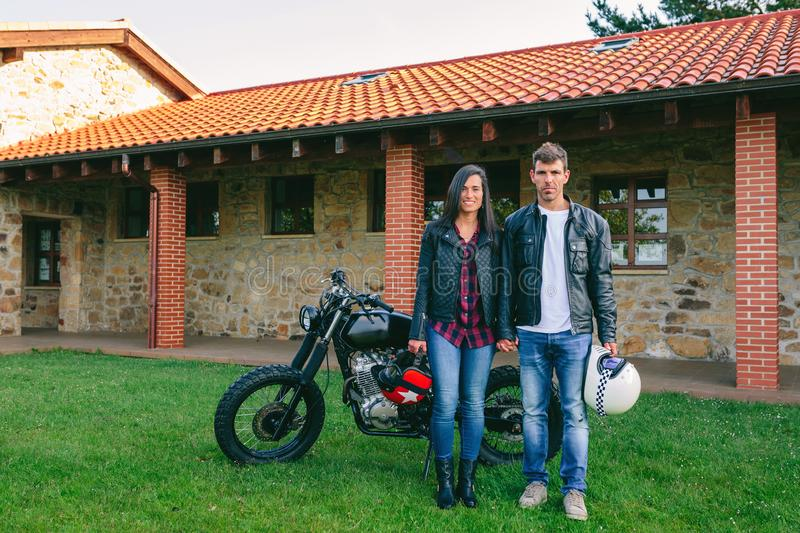 Couple posing holding hands and custom motorcycle. Young couple posing holding hands outdoors with custom motorcycle in the background stock image