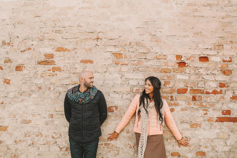 Young couple posing near the brick wall in the city stock images