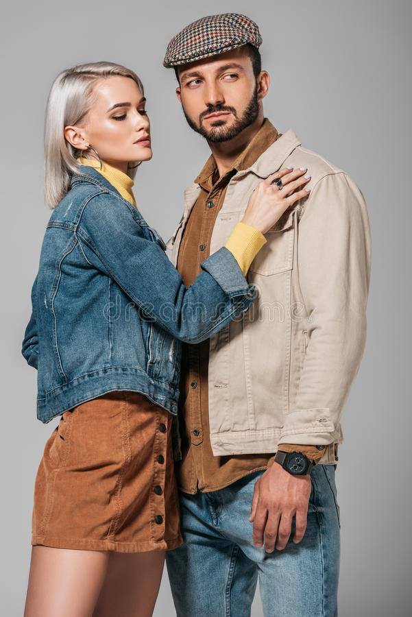 Young couple posing in street style autumn outfit. Isolated on grey stock photo