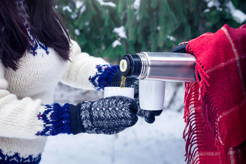 Young couple pours hot tea out of thermos in forest. Young couple pours hot tea out of thermos in winter forest stock photo