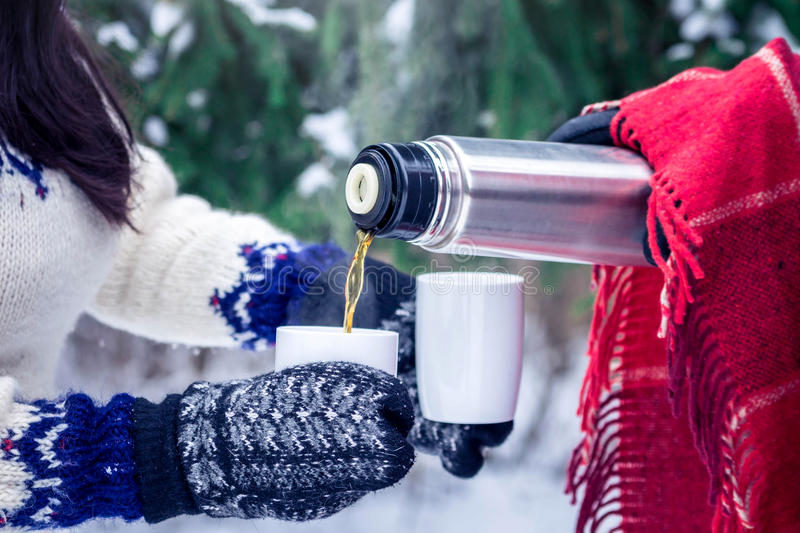 Young couple pours hot tea out of thermos in forest. Young couple pours hot tea out of thermos in winter forest stock images