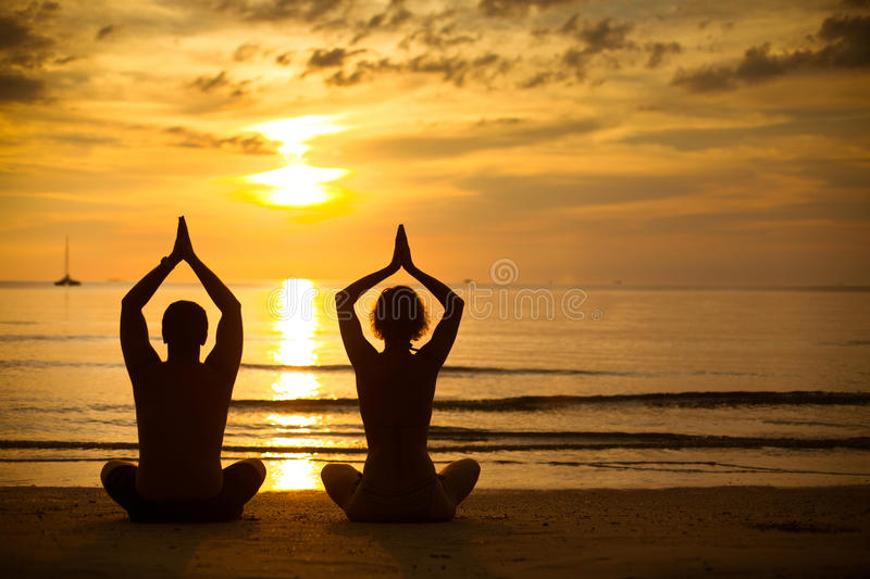 Young couple practicing yoga on beach at sunset stock photography