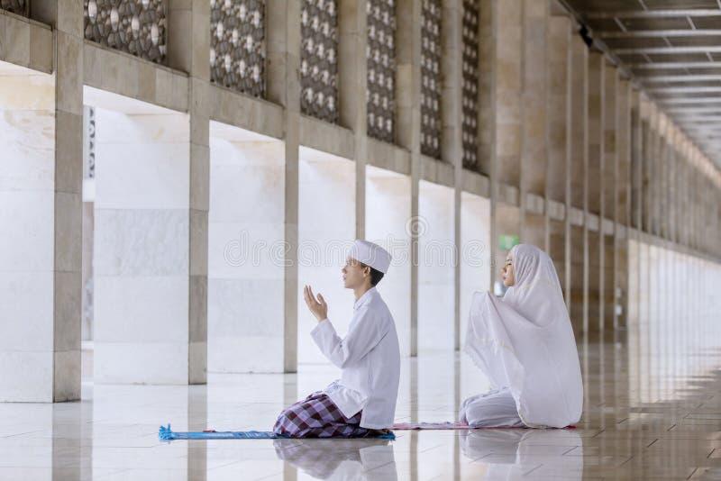 Young couple prays to the Allah after doing Salat stock photos