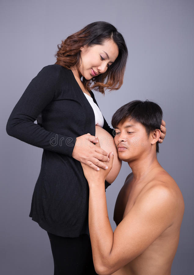 Young couple: pregnant mother and happy father on gray backgroun royalty free stock image