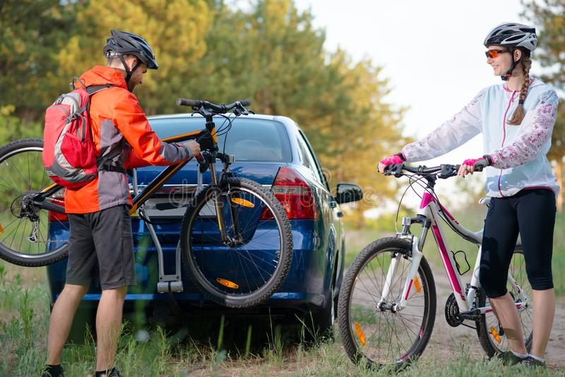 Young Couple Unmounting Mountain Bikes from Bike Rack on the Car. Adventure and Family Travel Concept. Young Couple Preparing for Riding the Mountain Bikes in stock photos