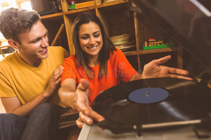 Young couple putting on a vinyl record. At home in the living room royalty free stock photos
