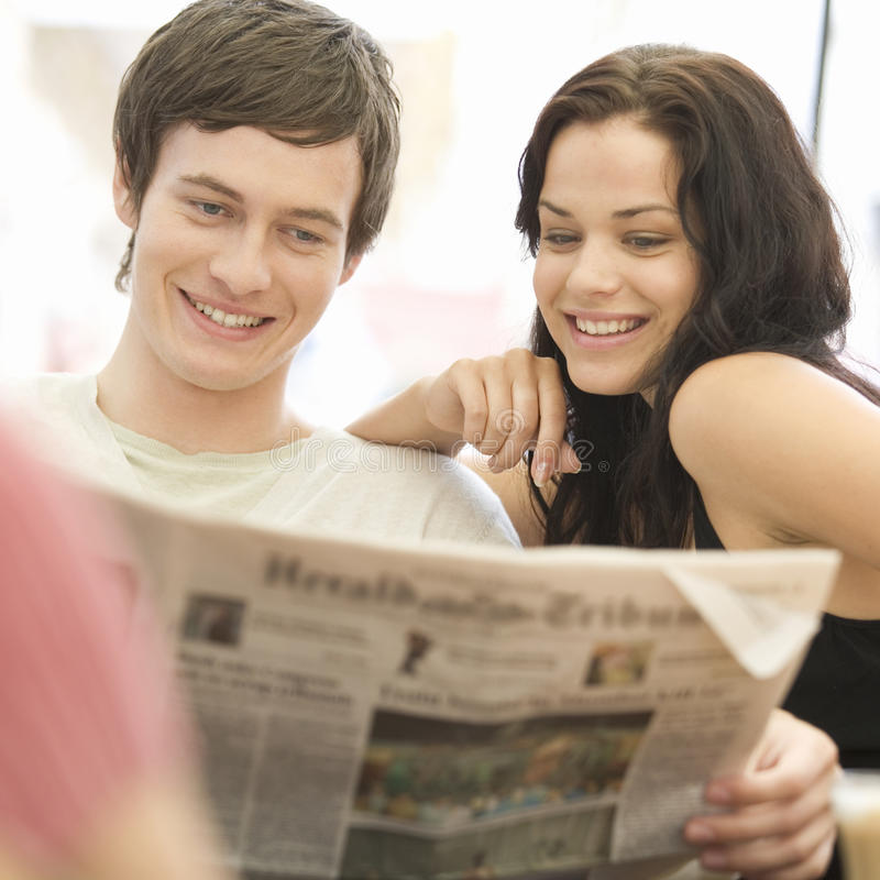A young couple reading the newspaper stock photos