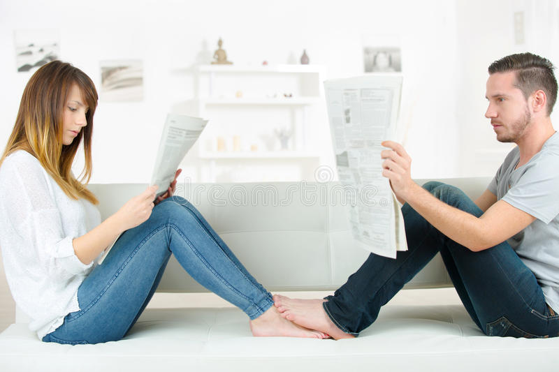 Young couple reading newspaper on sofa stock photo