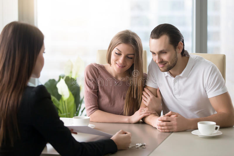 Young couple in real estate agency office meeting with agent royalty free stock images
