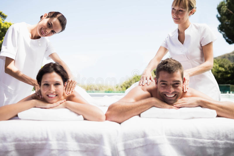 Young couple receiving a back massage from masseur. Portrait of relaxed young couple receiving a back massage from masseur in a spa stock image