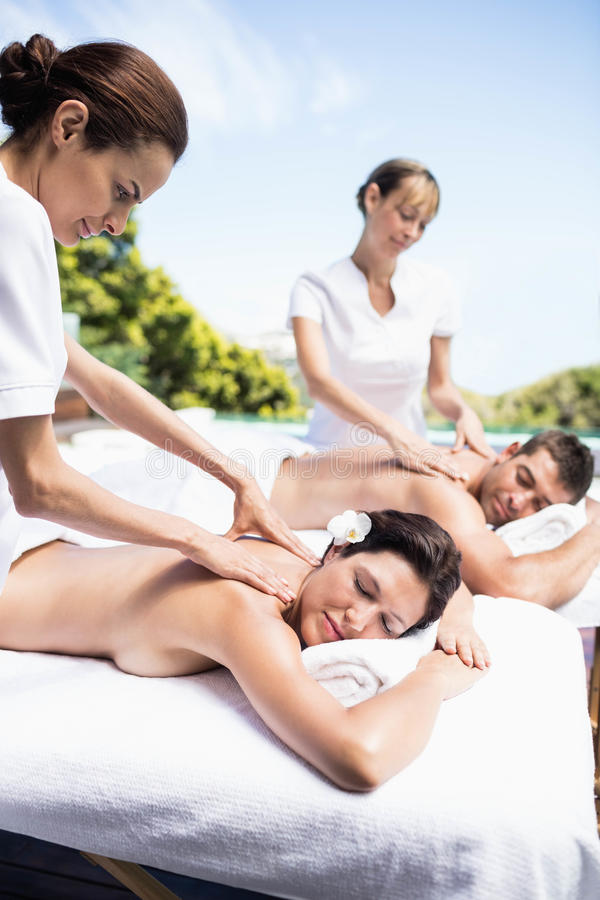 Young couple receiving a back massage from masseur. Relaxed young couple receiving a back massage from masseur in a spa royalty free stock photography