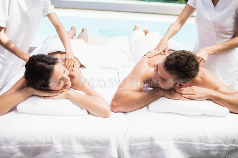 Young couple receiving a back massage from masseur. Relaxed young couple receiving a back massage from masseur in a spa stock photography