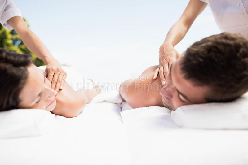 Young couple receiving a back massage from masseur. Relaxed young couple receiving a back massage from masseur in a spa stock photos