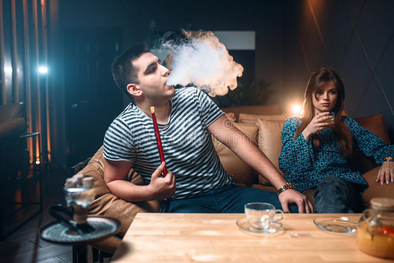 Young couple relax and smoking hookah stock image