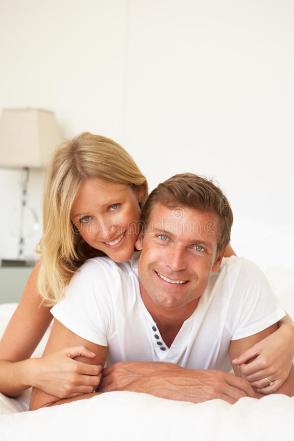 Download Young Couple Relaxing On Bed Stock Photo - Image of length, home: 14922670