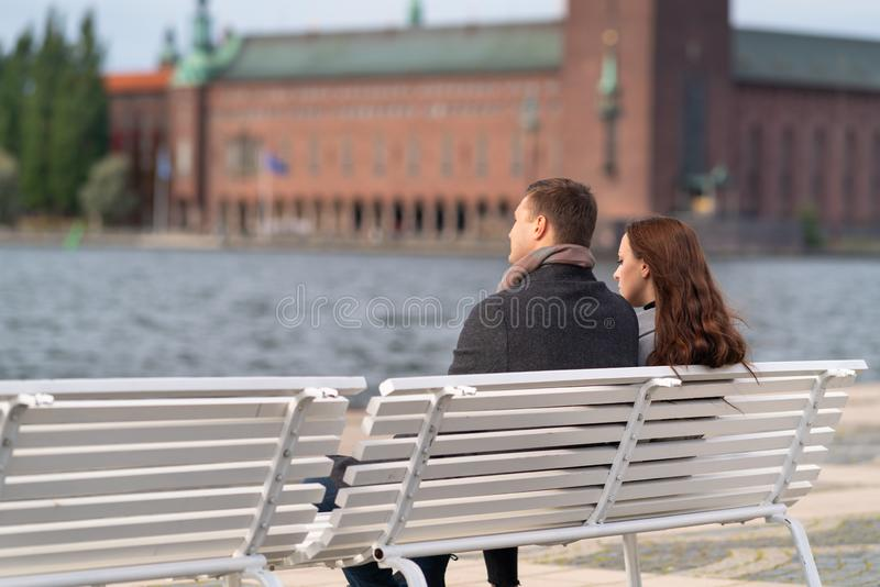 Young couple relaxing on a bench enjoying sunset stock image