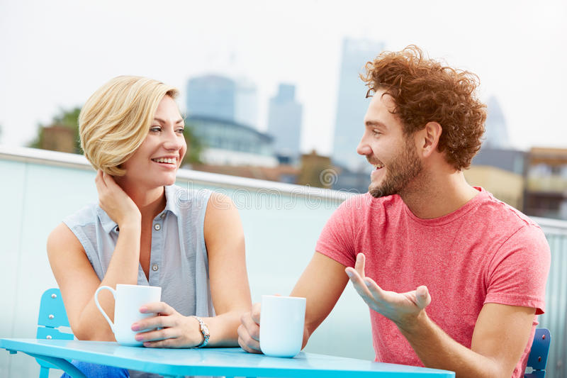 Young Couple Relaxing With Coffee On Roof Terrace. Sitting Down Chatting To Each Other royalty free stock photography