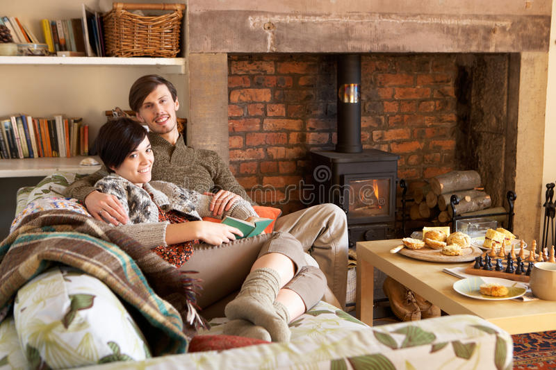Young couple relaxing by fire royalty free stock images