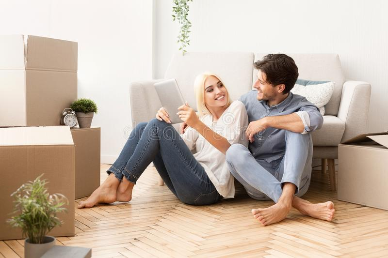 Young Couple Relaxing On Floor Using Digital Tablet royalty free stock photos