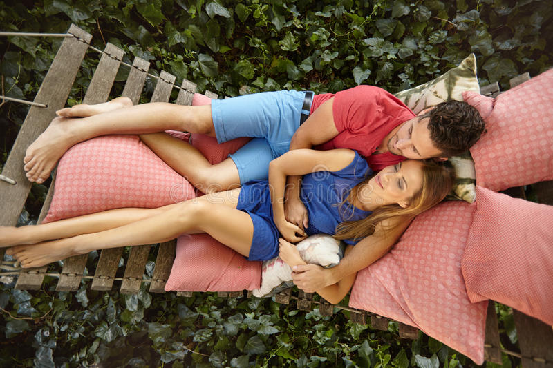 Young couple relaxing on a garden hammock. Top view of young couple lying on a garden hammock. Young men embracing his girlfriend relaxing in backyard garden stock image