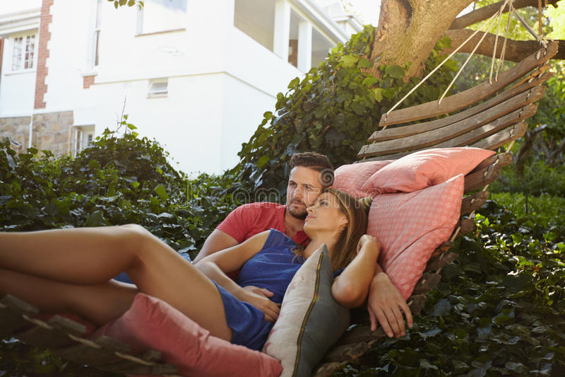Young couple relaxing on a hammock. Young couple relaxing on a garden hammock. They are looking away in thought. Relaxed men and women swinging on a hammock in royalty free stock images