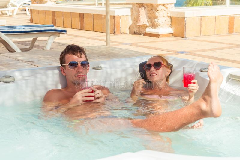 Young couple relaxing in jacuzzi pool stock images