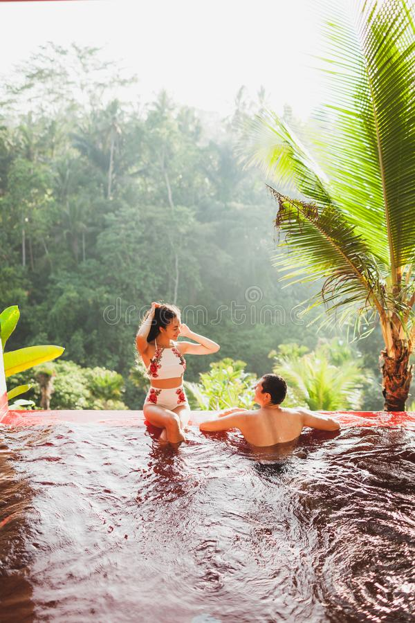 Young couple relaxing luxury private infinity pool royalty free stock photos