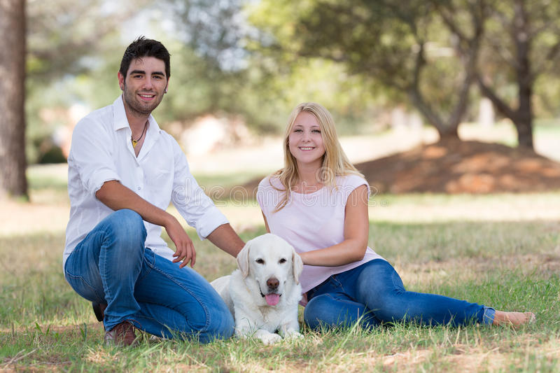 Young couple relaxing with old senior labrador dog in the nature royalty free stock image