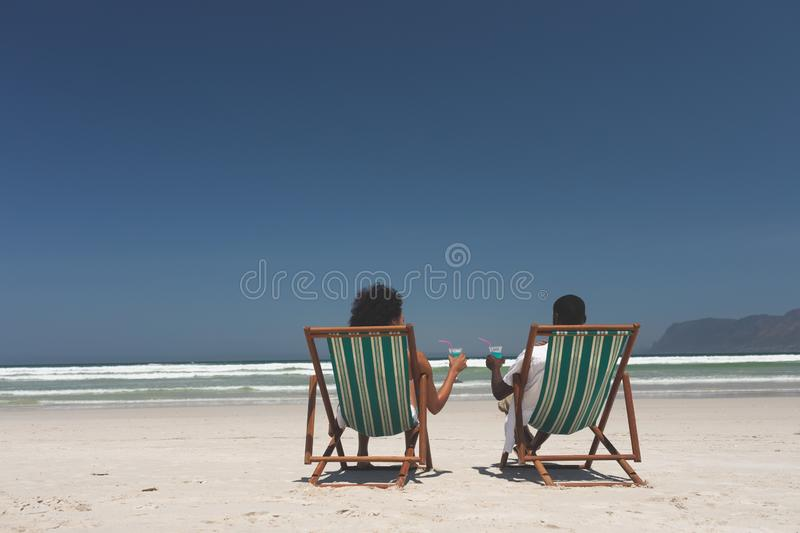 Young couple relaxing on sun lounger at beach on sunny day. Rear view of young multi-ethnic couple relaxing on sun lounger at beach on sunny day, They are stock photography