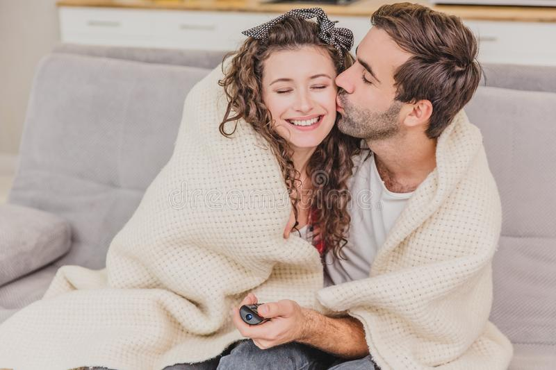 Young couple relaxing in their apartment, sitting on the couch, watching TV. Covered with a blanket, happy hugging. Kiss on the cheek royalty free stock photo