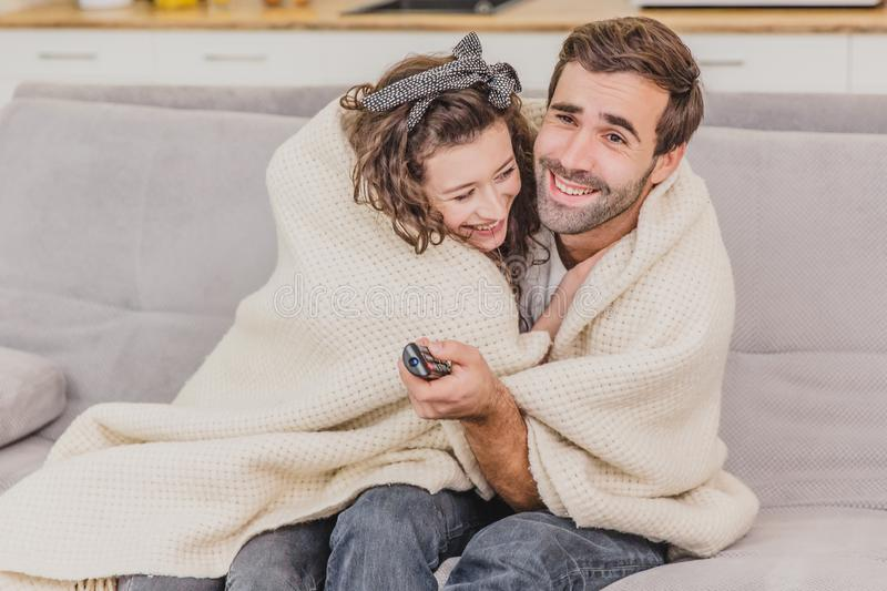 Young couple relaxing in their apartment, sitting on the couch, watching TV. Covered with a blanket, happy hugging. Smiling stock photo