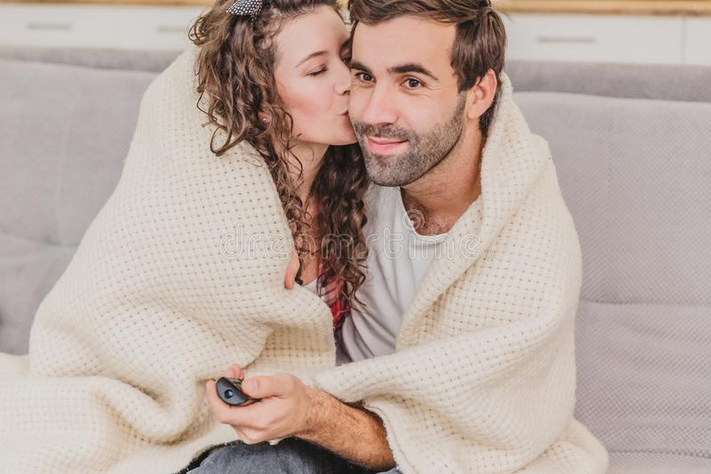 Young couple relaxing in their apartment, sitting on the couch, watching TV. Covered with a blanket, happy hugging. Kiss on the cheek royalty free stock photography