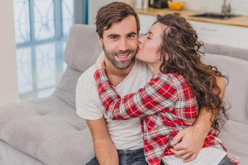 Young couple relaxing in their apartment, sitting on the couch, watching TV. Lovers and happy hug. Kiss on the cheek. Young couple relaxing in their apartment royalty free stock photography