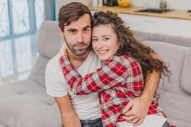 Young couple relaxing in their apartment, sitting on the couch, watching TV. Lovers and happy hug. Look straight into. Young couple relaxing in their apartment stock photography