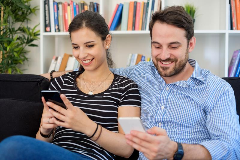 Young couple relaxing and using smartphone at home stock image
