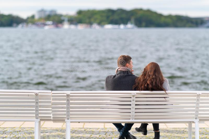 Young couple relaxing on a waterfront promenade. stock photo