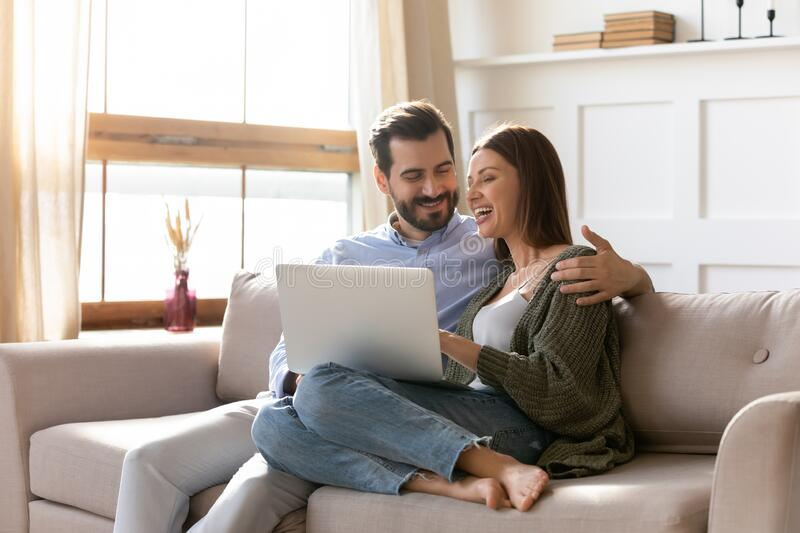 Young couple rest on sofa browsing internet on modern laptop. Overjoyed young husband and wife relax on sofa in living room browsing wireless Internet on laptop stock images