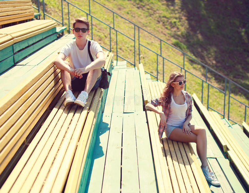 Young couple resting on the bench, youth, teenagers, fashion concept royalty free stock photography