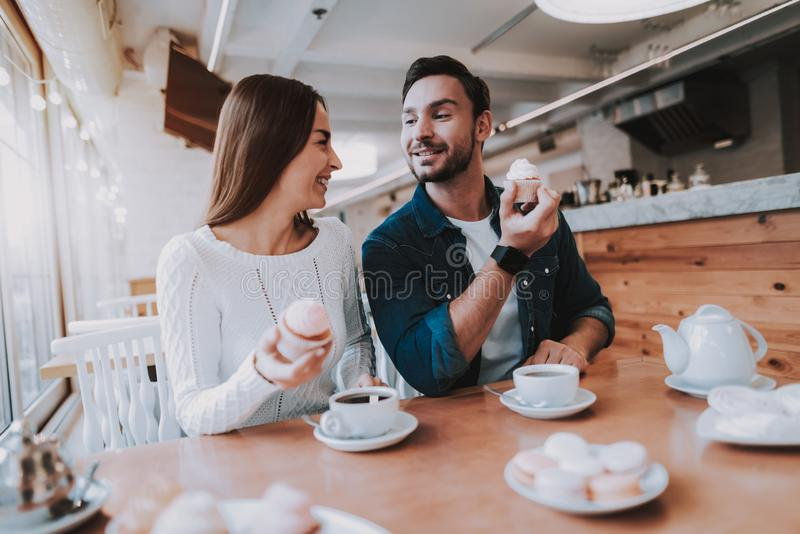 Young Couple is Resting in Cafe. Couple Resting in Cafe. Couple is Beautiful Young Man and Woman. Couple is Eating Cakes and Drinking a Tea. Persons is Sitting royalty free stock photos