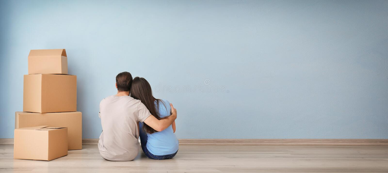 Young couple resting near boxes indoors. Moving into new house royalty free stock images