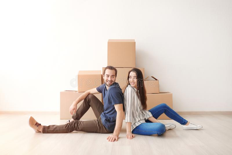 Young couple resting near boxes indoors. Moving into new house stock photo