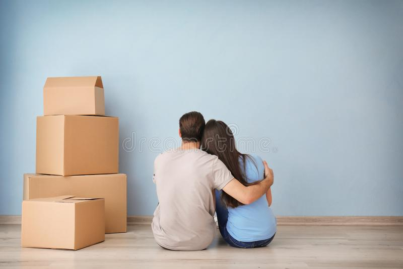 Young couple resting near boxes indoors. Moving into new house royalty free stock photos
