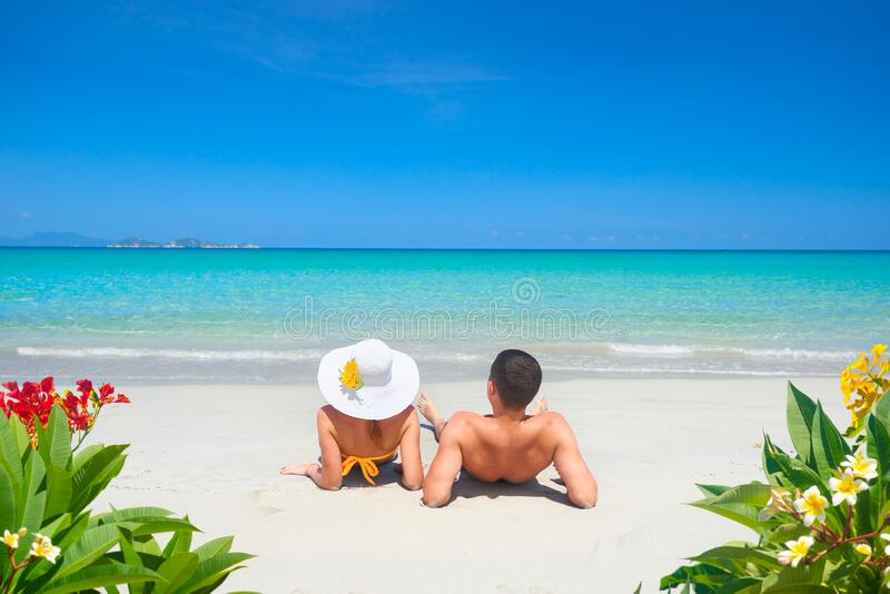 Young couple resting on tropical beach on summer sunny day on background of clear blue sky and turquoise sea. stock image