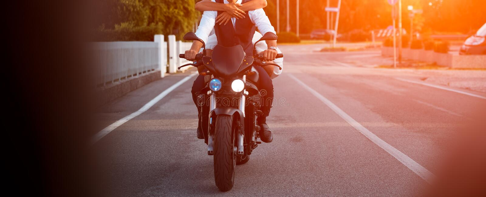 Young couple ridind motorcycle on city road at sunset stock image