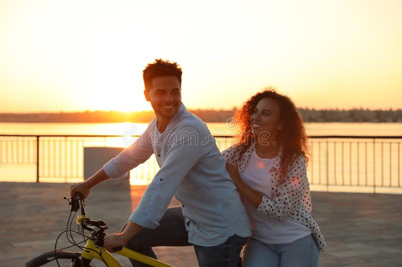 Young couple riding bicycle on city waterfront stock image