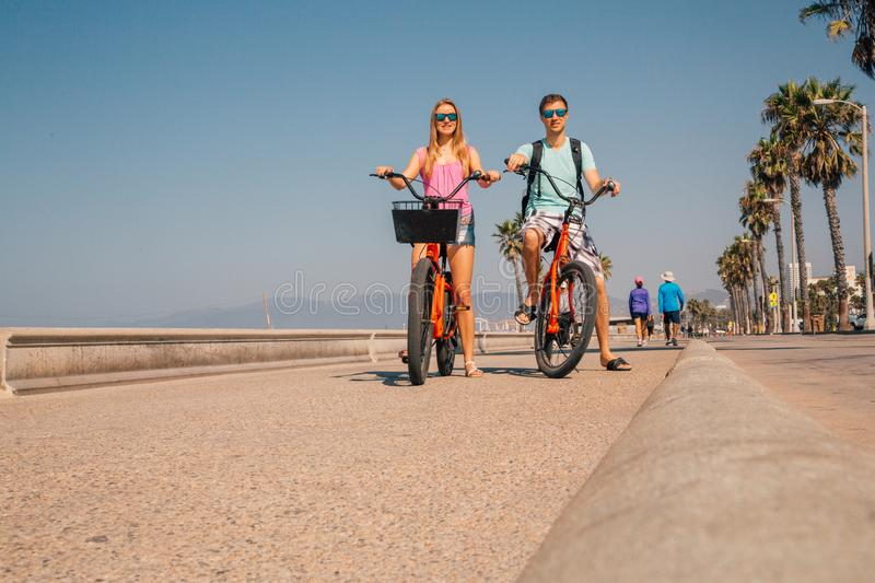 Young couple riding bicycles down the Venice beach in Los Angeles stock photos
