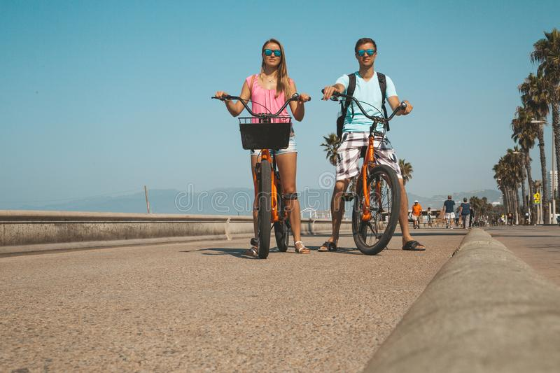 Young couple riding bicycles down the Venice beach royalty free stock image