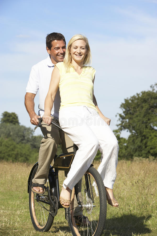 Young couple riding bike in countryside royalty free stock image