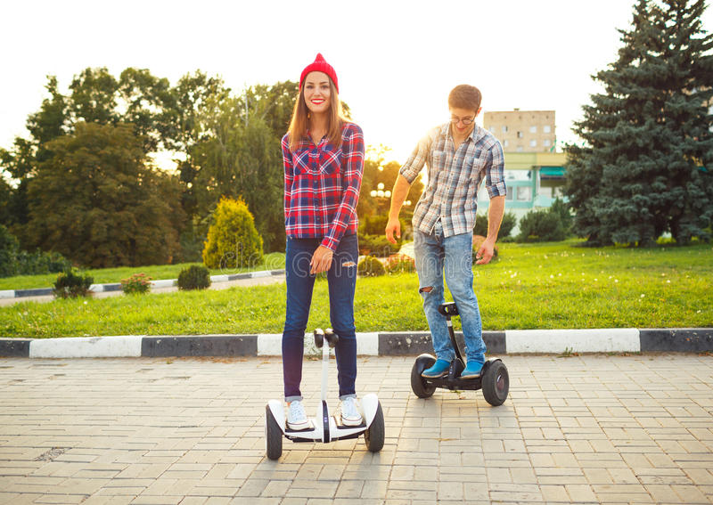 Young couple riding hoverboard - electric scooter, personal eco royalty free stock images