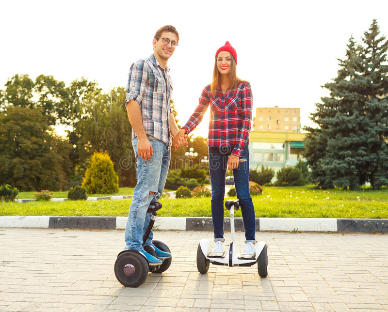 Young couple riding hoverboard - electrical scooter, personal ec royalty free stock images